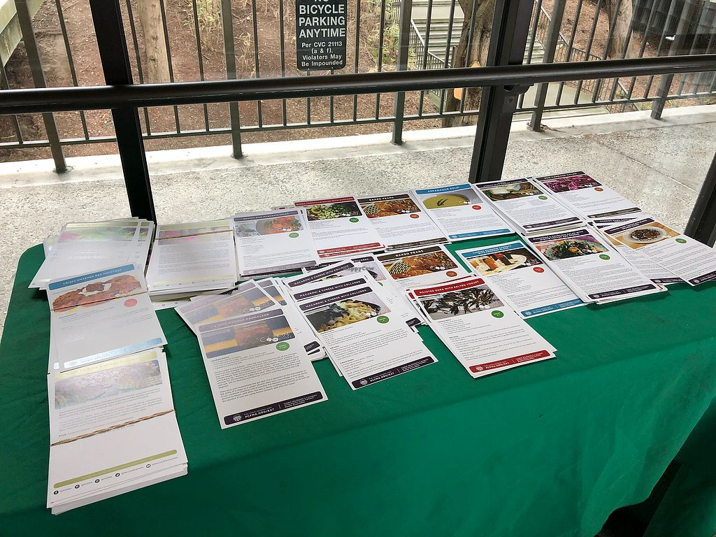 """Photo of Parnassus Farmers' Market  by <a href=""""/members/profile/BrittanyHowze"""">BrittanyHowze</a> <br/>Table at the market with recipes set out on it <br/> April 18, 2018  - <a href='/contact/abuse/image/31958/387729'>Report</a>"""