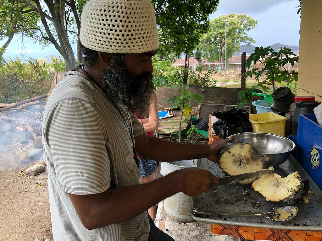 """Photo of Ital Creations - Food Stall  by <a href=""""/members/profile/skl411"""">skl411</a> <br/>Cutting the roasted breadfruit <br/> April 17, 2018  - <a href='/contact/abuse/image/43557/387161'>Report</a>"""