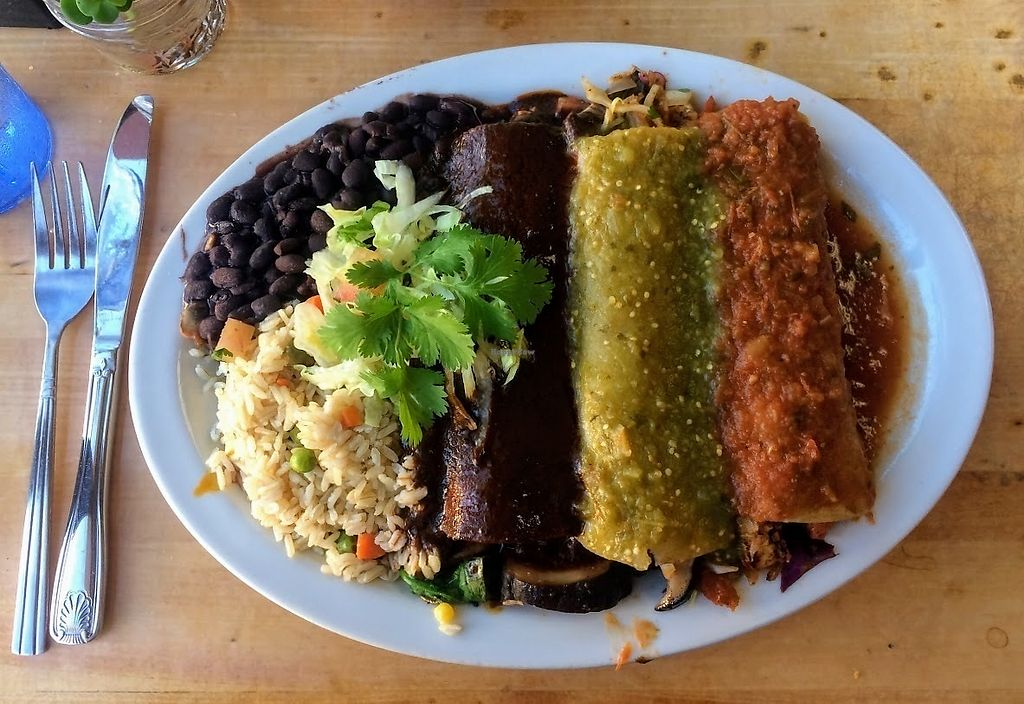 """Photo of Hugo's Cocina   by <a href=""""/members/profile/fullbellyhappyheart"""">fullbellyhappyheart</a> <br/>Trio of Veggie Enchiladas. Tempeh with roja salsa, mushroom with verde, and spinach with mole, served with rice and beans <br/> June 20, 2017  - <a href='/contact/abuse/image/88374/271196'>Report</a>"""